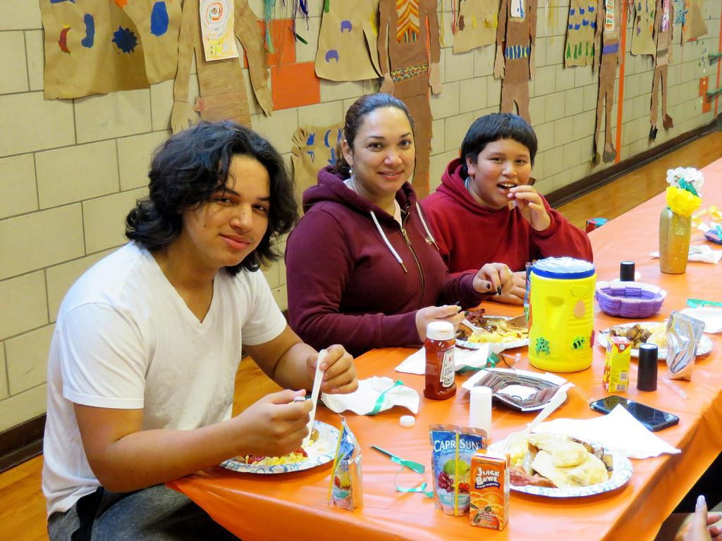 Three family members seated inside the Devens Gymnasium for the Thanksgiving Brunch