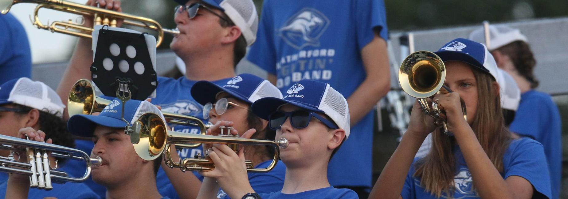 Band students playing instruments at a football game