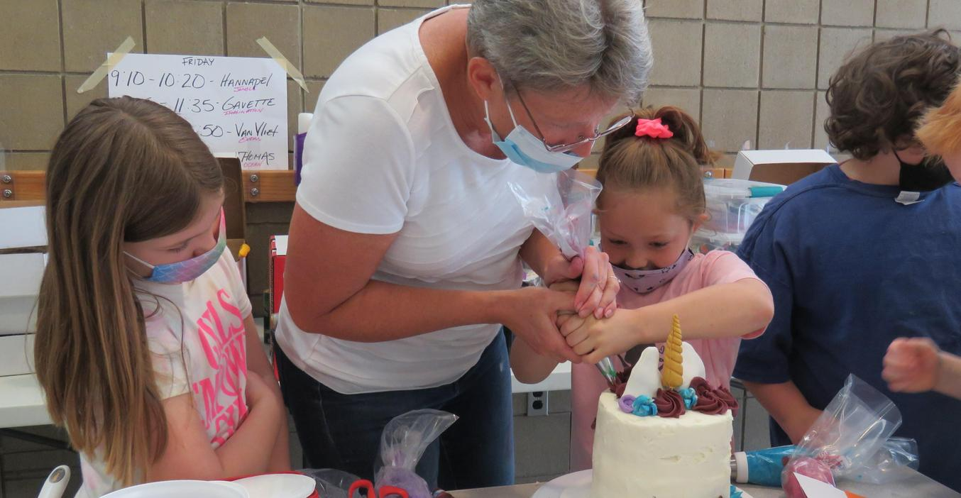 Students learn how to use the frosting piping bag to make decorations on the cake.