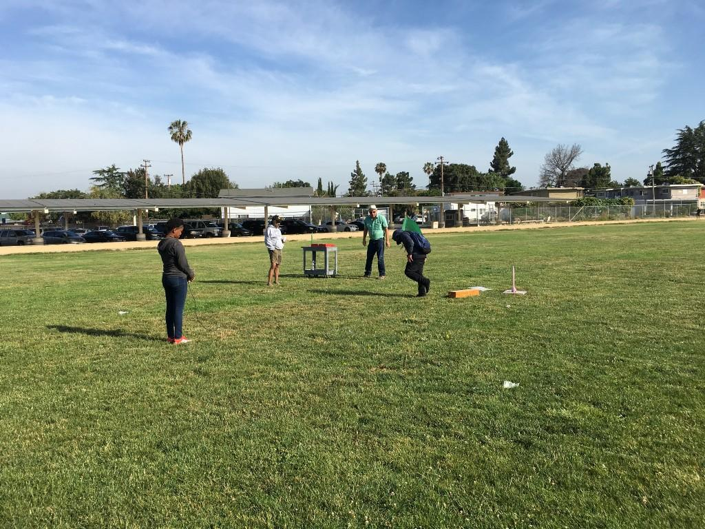 teachers and students in a large green field setting up their rockets