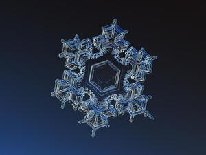 macro six pointed snowflake on blue background