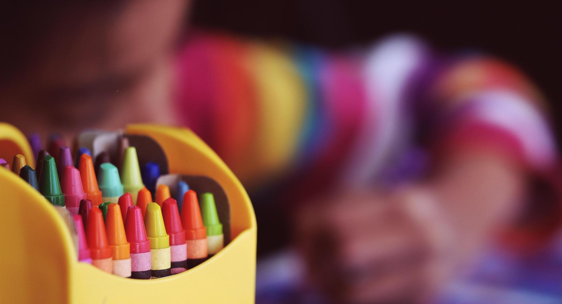 a box of crayons is in focus while a girl, out of focus, colors in the background.