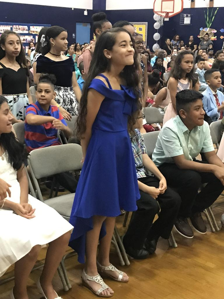 several 5th graders standing up being recognized for academic achievements