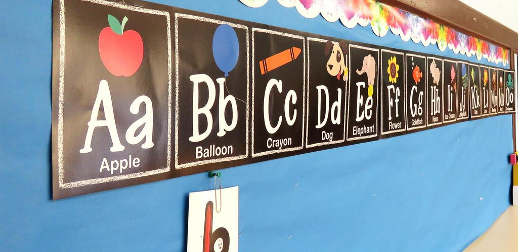The letters of the alphabet hung on the wall of an Adams School classroom. 'A is for Apple,' 'B is for Balloon', and so on