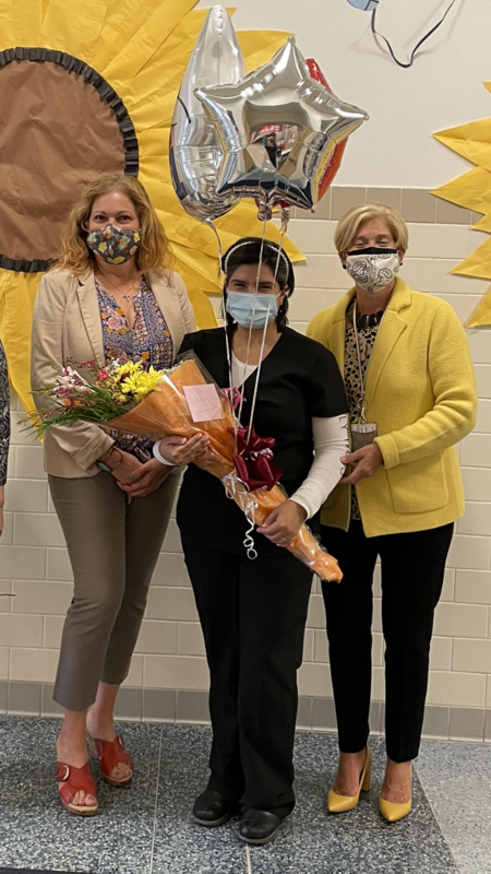 Nurse Sanchez holding her balloons and flowers and posing with two women