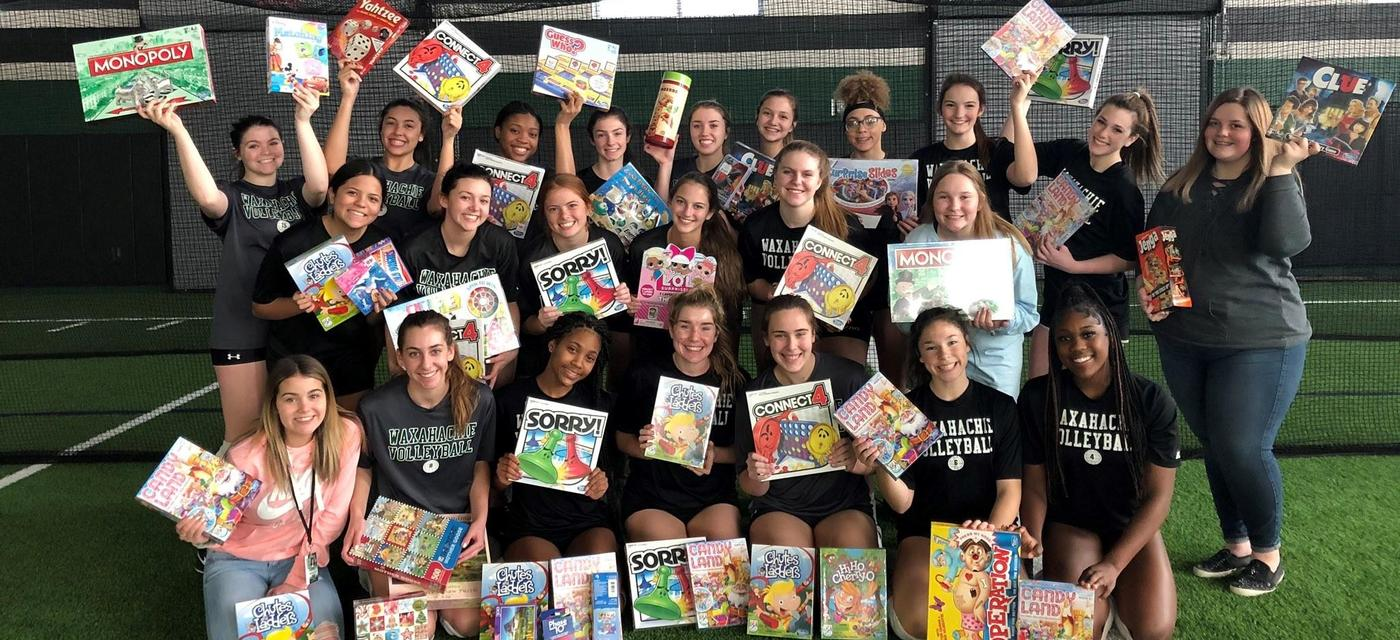 Volleyball players with games donated for Toy Drive