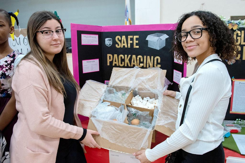 Two students hold a container for safe packaging