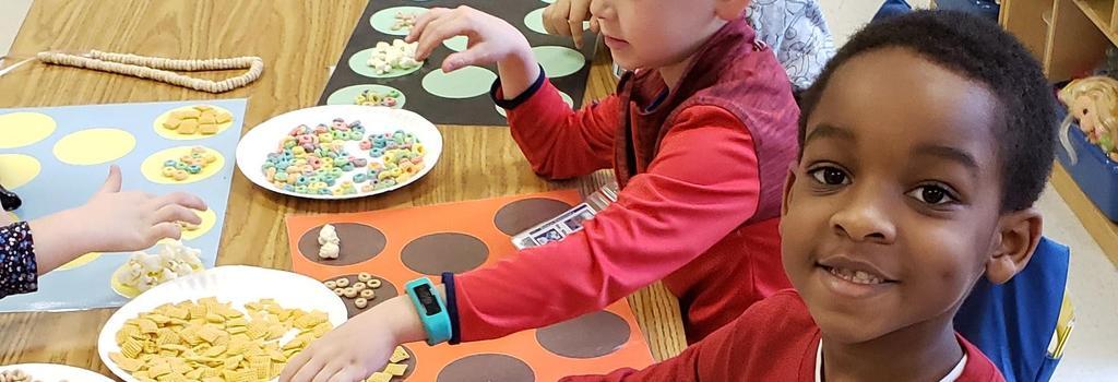 Kindergarten students counting cereal