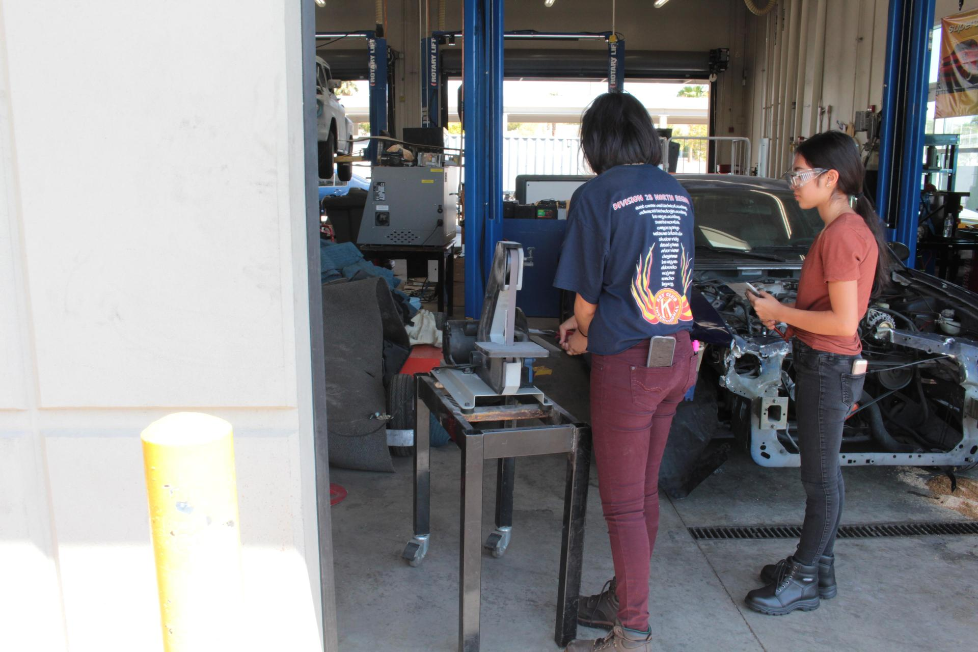 Two female students checking out a vehicle