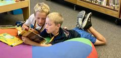 Boys enjoying reading a book together