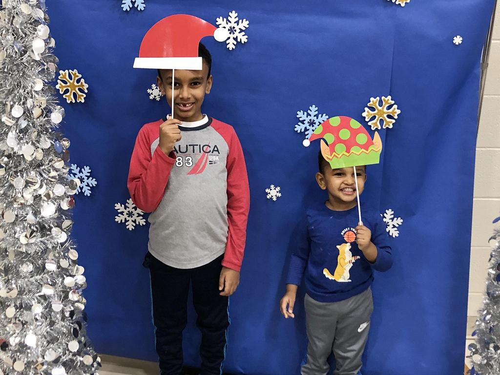 Two brothers, at the photo station, both holding decorative paper Santa hats over their heads