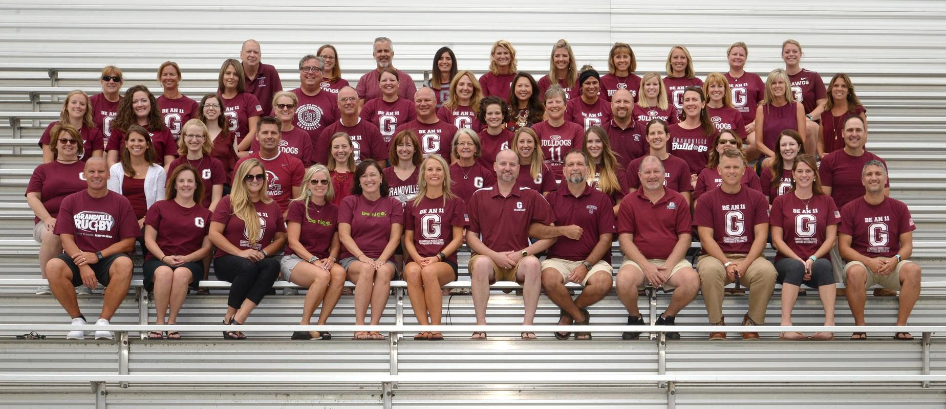 photo of staff of GMS sitting on bleachers in maroon shirts