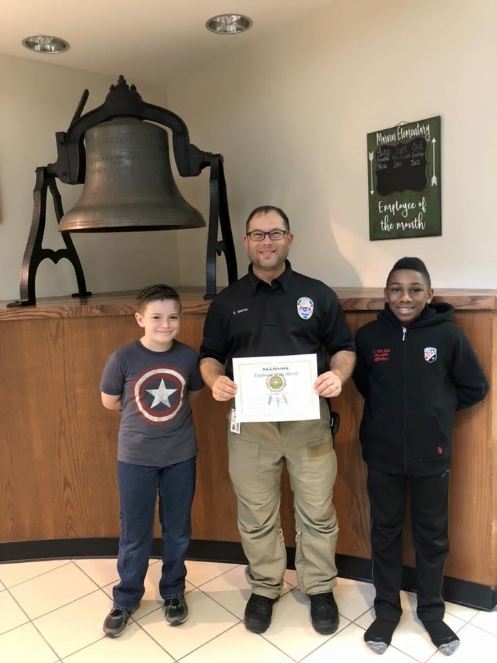 security officer poses with 2 students