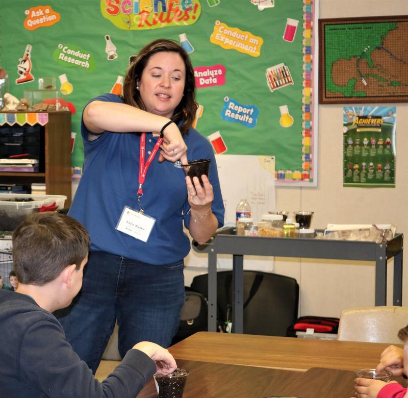 Teacher demonstrating seed planting.