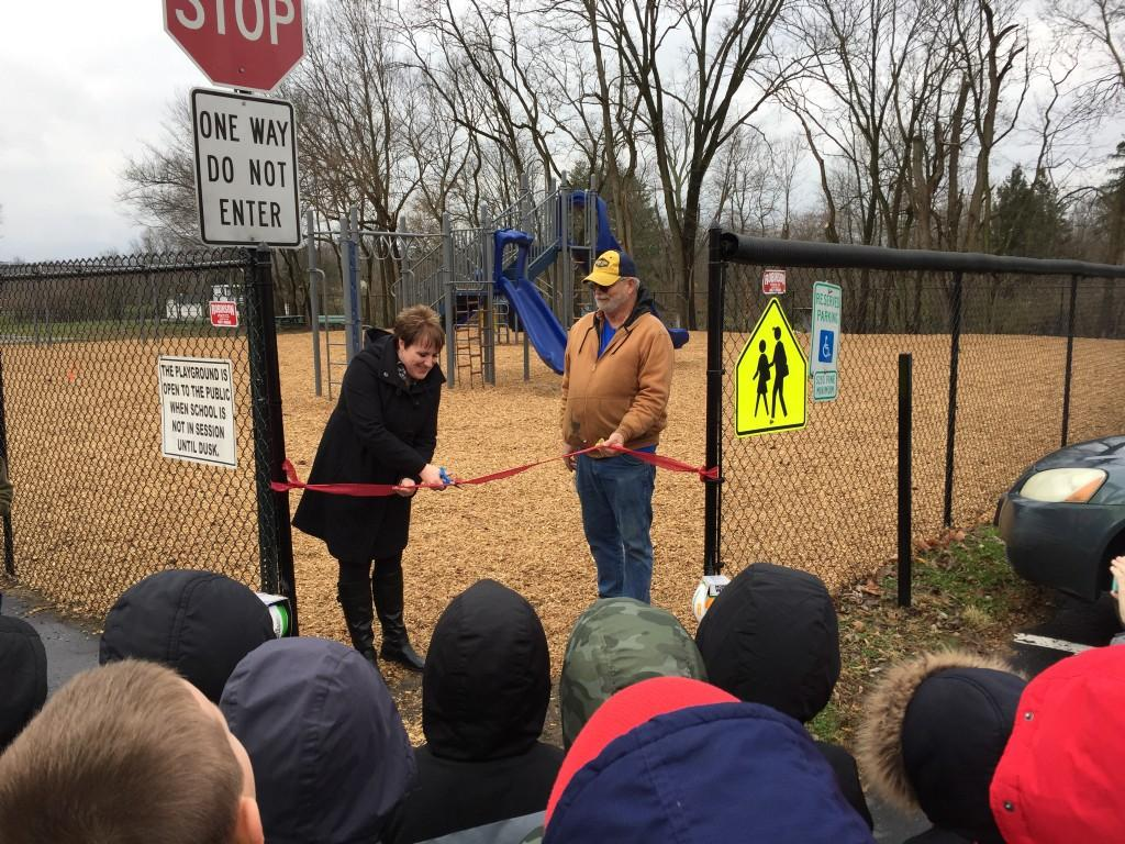 Mrs. Harrison cuts the ribbon for the new SME Playground.