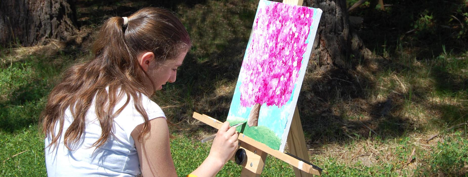 Student painting an apple tree in blossom at an easel outside.