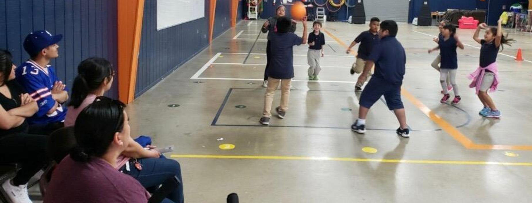 Image of parents watching students playing basketball.