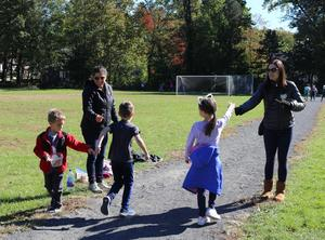 Washington School parents encourage students running laps as part of the Recess Runners Club, handing them popsicle sticks they can then turn in for plastic charms once a mile is reached.