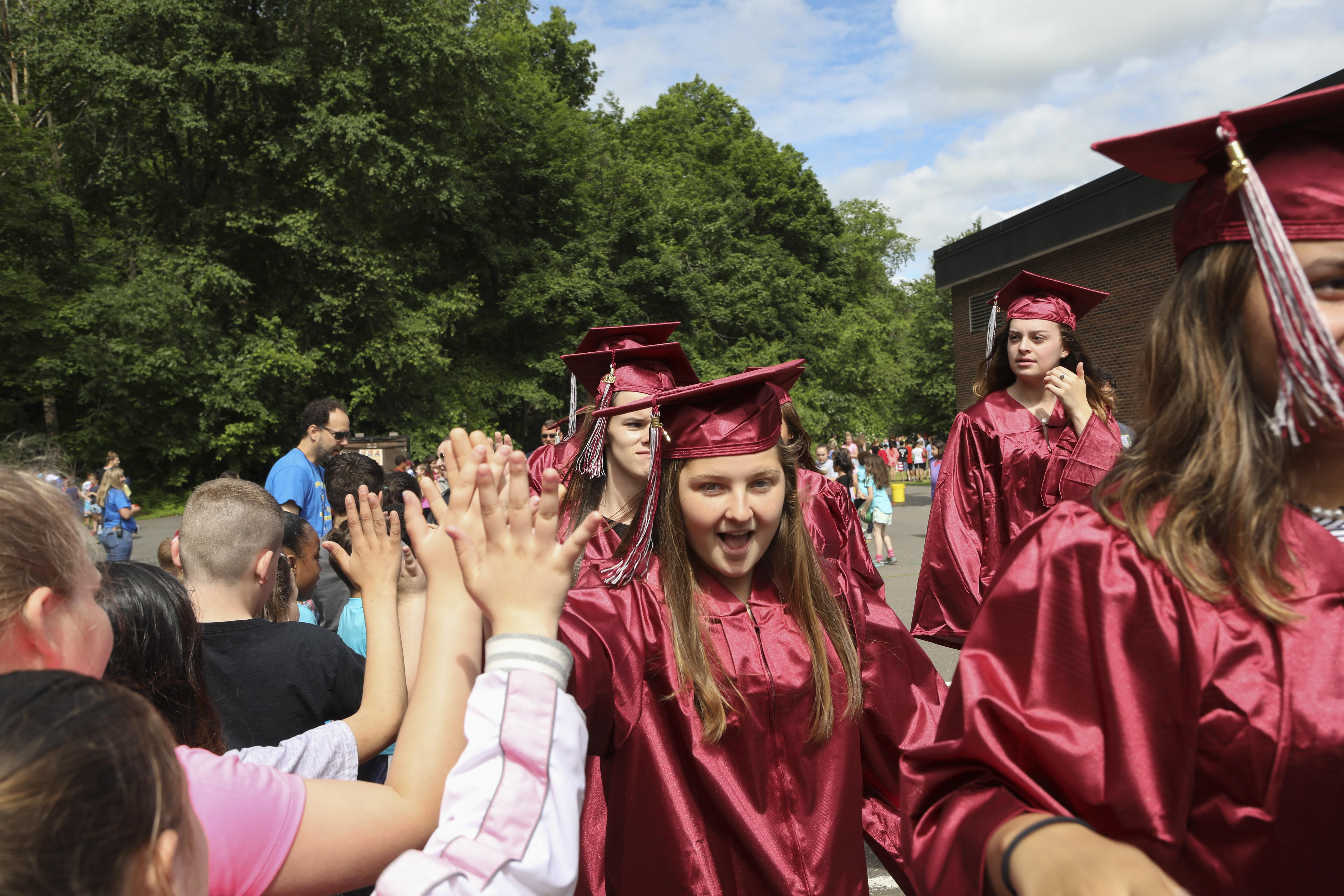 Grad walk - High School graduates get high-fives from elementary students