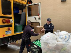 Firefighters help load buses with food.