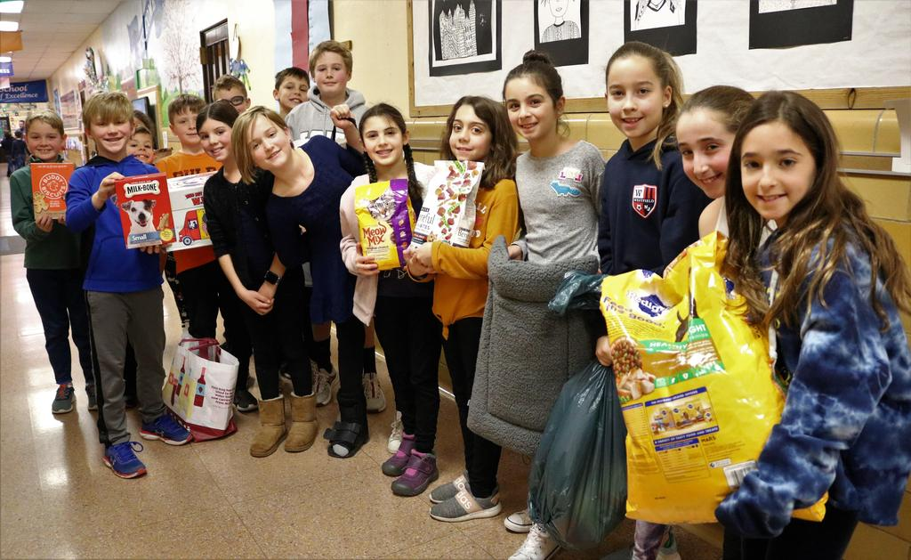 Photo of group of Wilson 4th graders holding pet food and other items for local animal shelter, collected during Wilson's Month of Hope.
