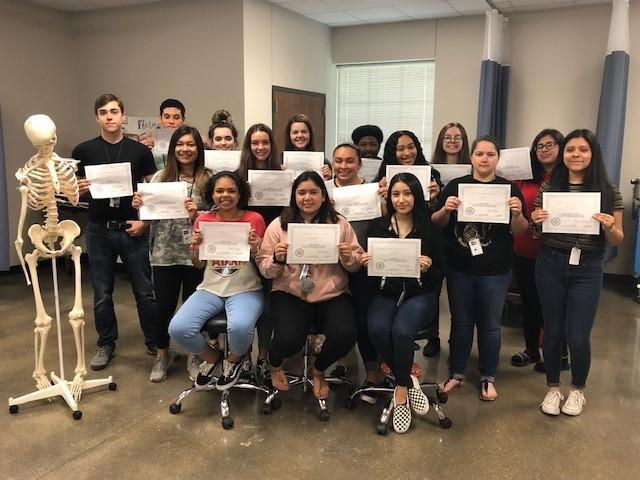 health science students pose with certificates and skeleton