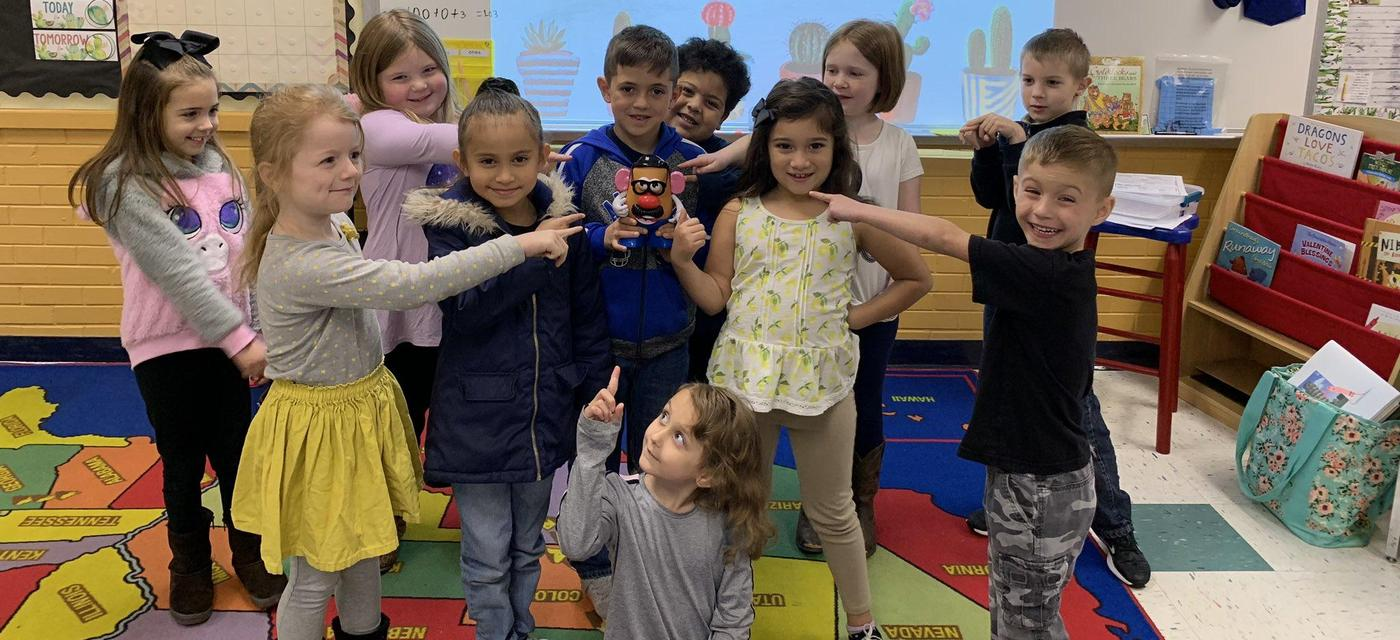 group of students all pose pointing at Mr. Potato Head