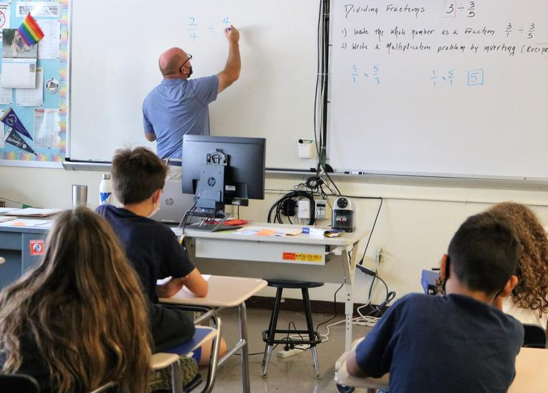 Extended School Year teacher Douglas Kehler reviews fractions with 6th graders during an ESY mathematics course