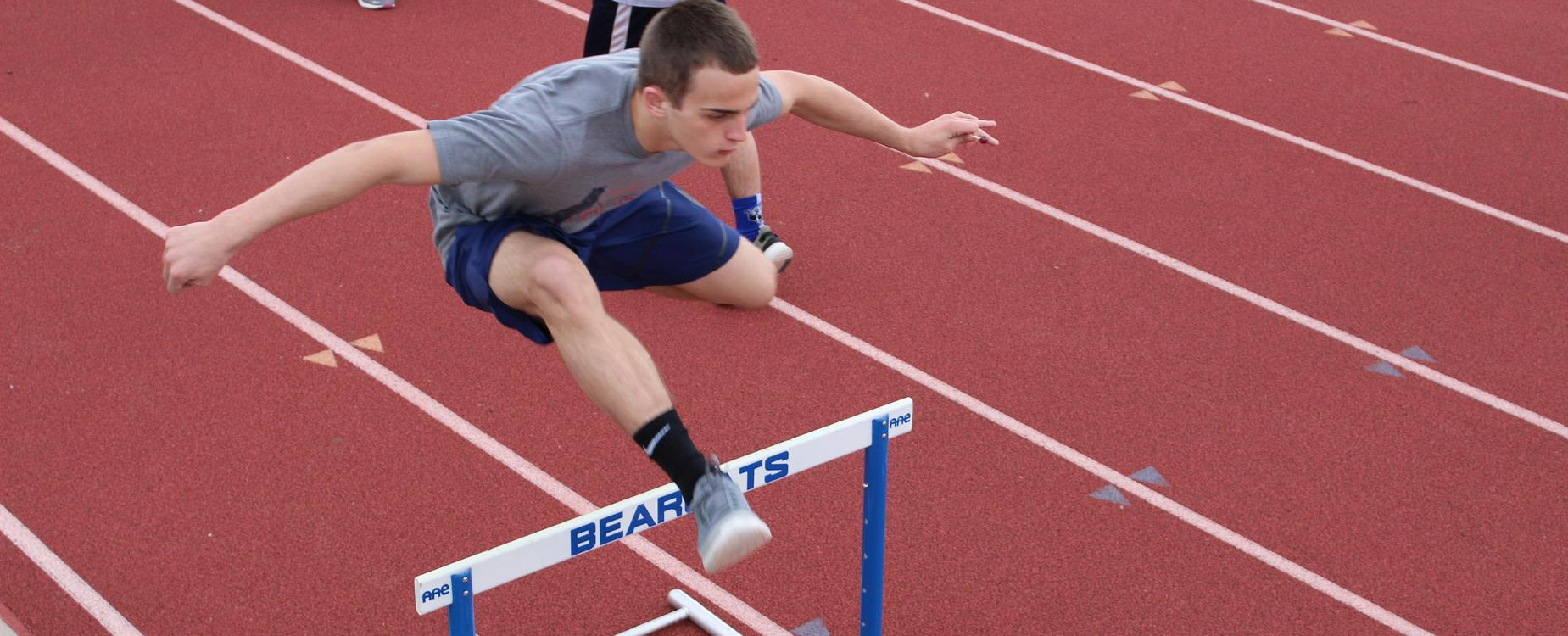 Student jumping hurdles in an event