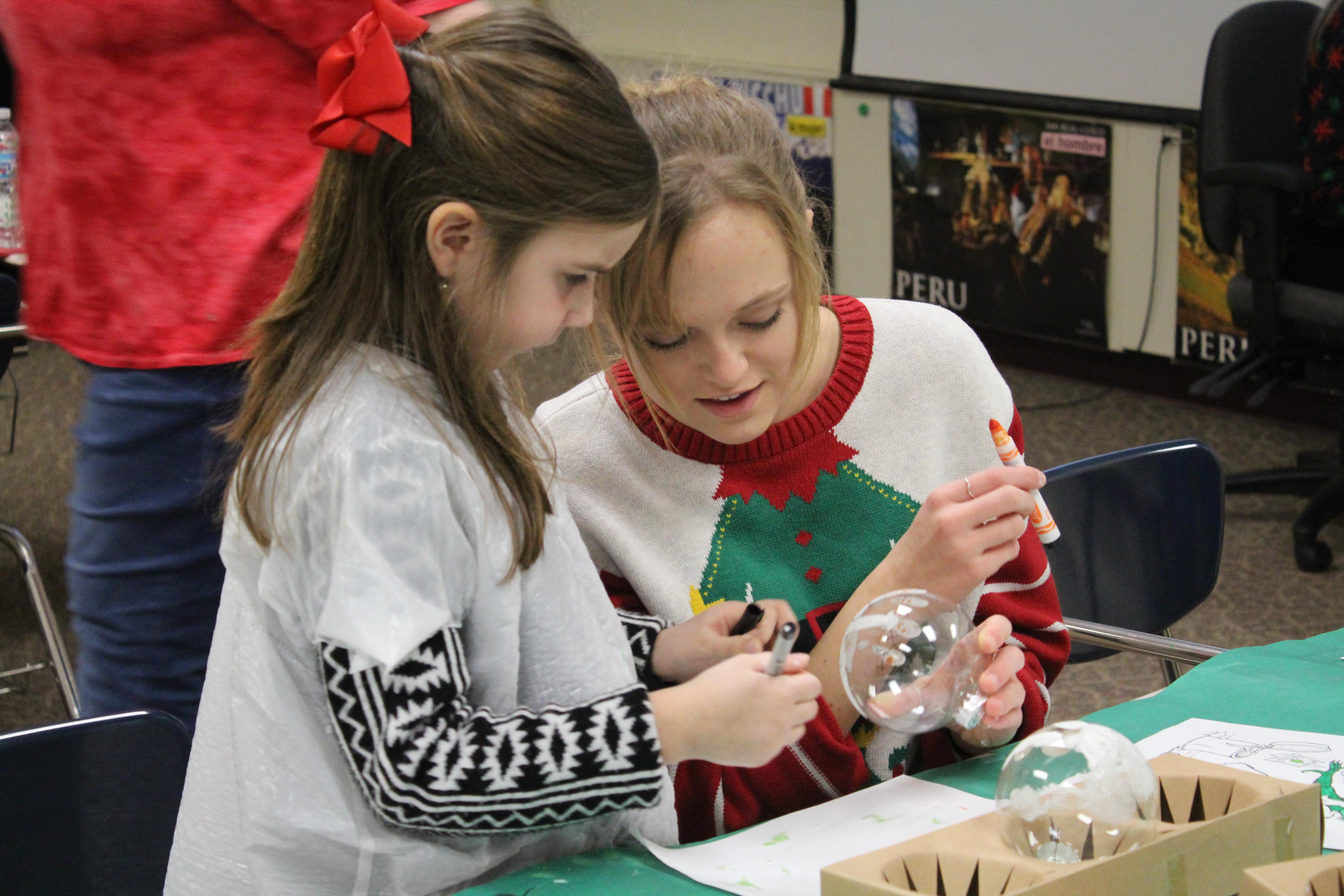 Teen girl wearing Christmas sweater helping a young child cut decorate a Christmas bulb