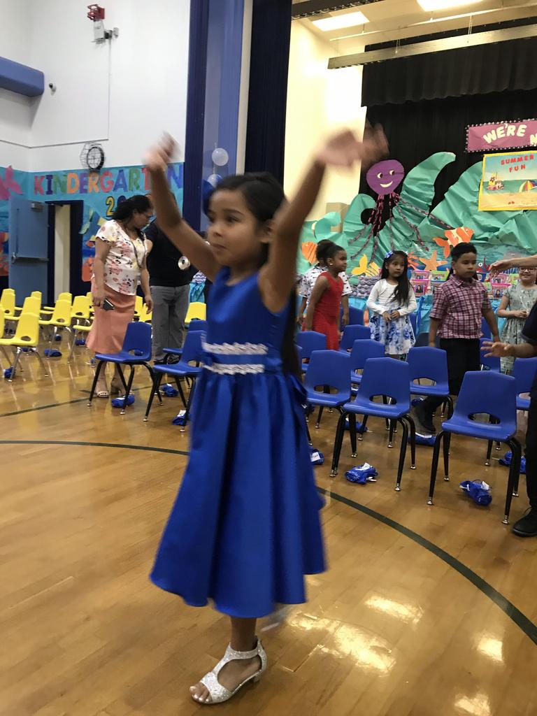 girl with blue dress with hands up in the air