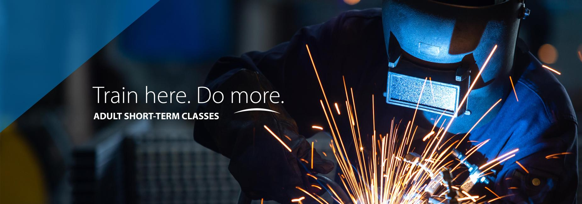 Image of a person welding with sparks flying and text that reads: Train here. Do more. Adult short-term classes
