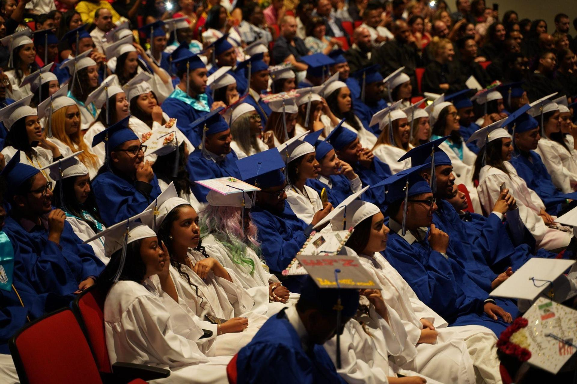 Students in white and blue gowns in graduation