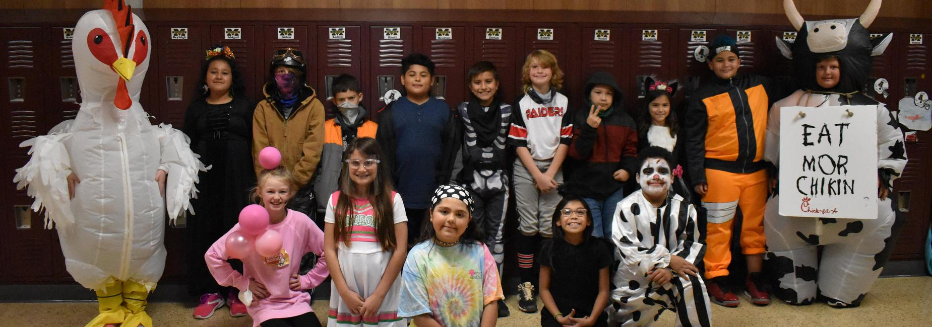 Elementary students pose with Halloween costumes