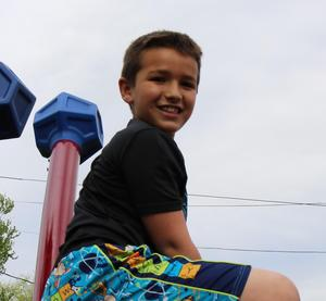 Photo of a McKinley student enjoying new playground equipment.