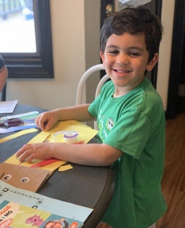 smiling boy wearing green tshirt making a brown bag puppet