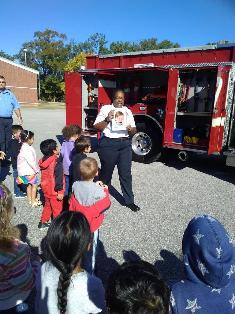 Fire and Life Safety Educator talks to students with fire truck in the background.
