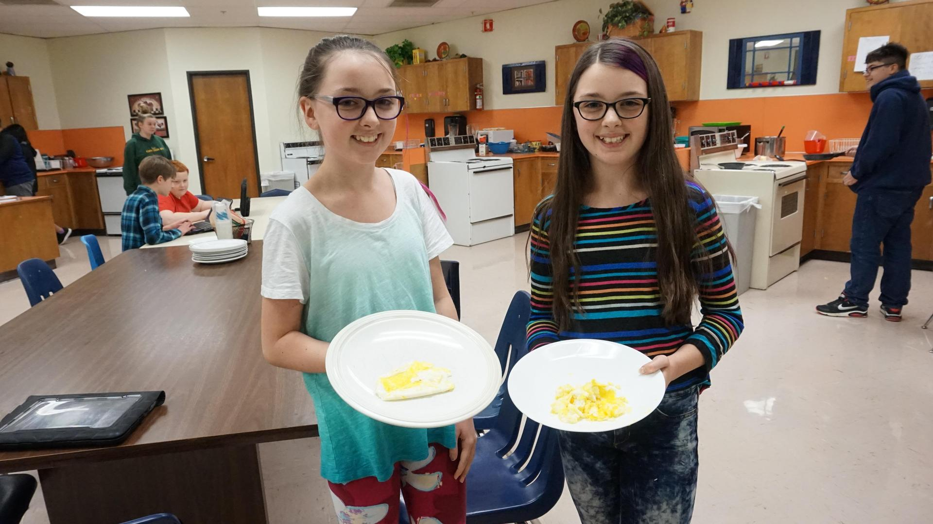 Two female students showing off their cooked eggs