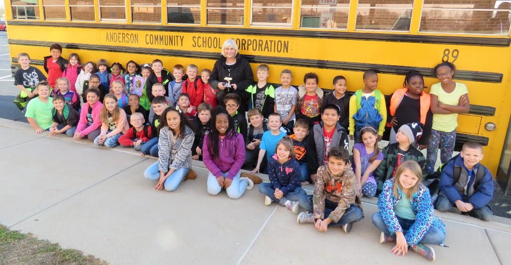 students standing and sitting next to school bus