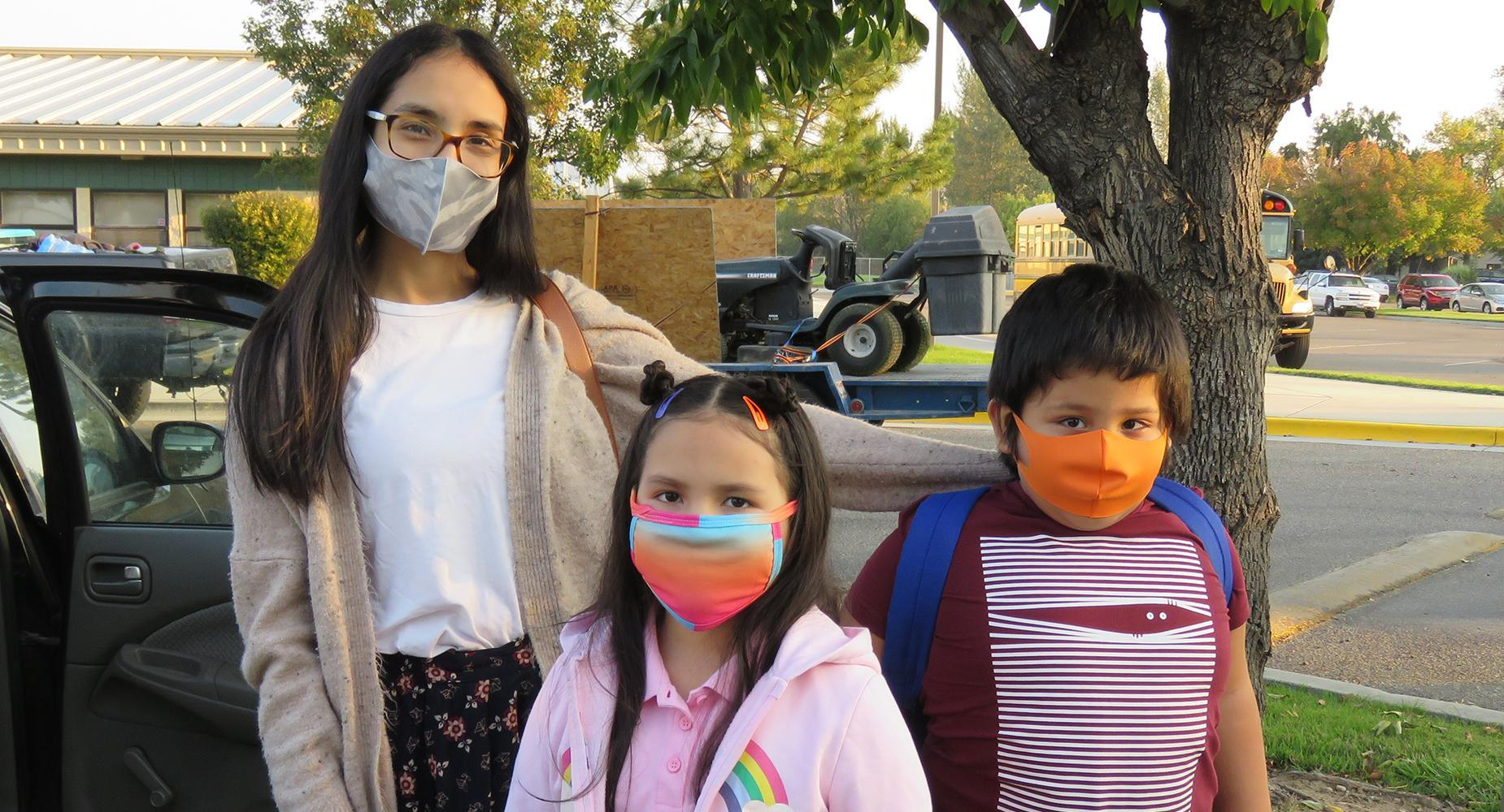 Mother, daughter and son, in bright masks, in front of Iowa Elementary