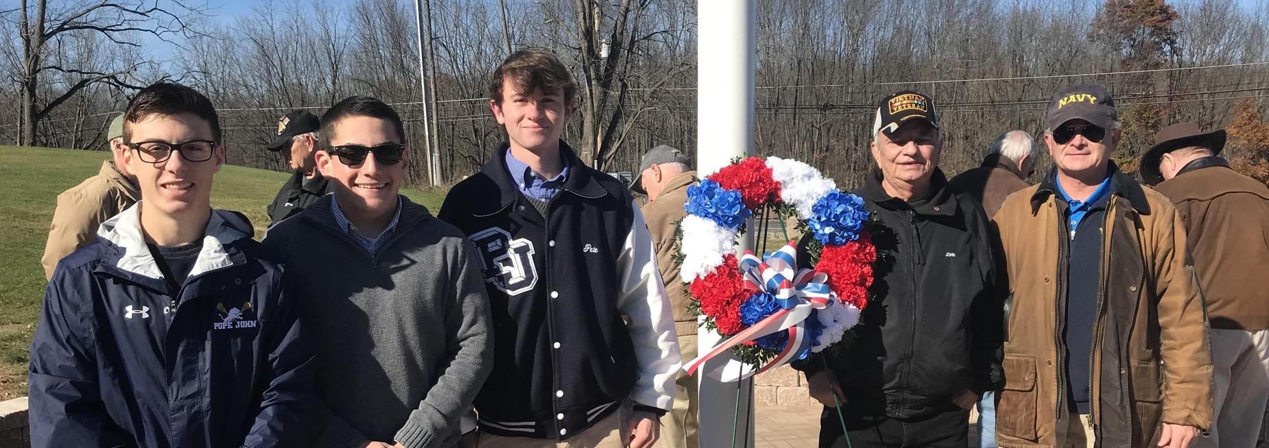 Pope John students pose in front of flagpole at Veterans Cemetery