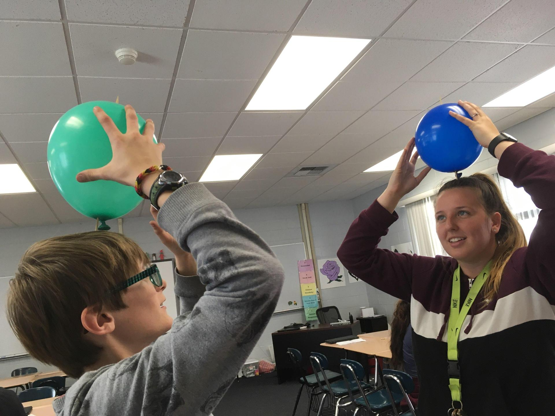 a student and program leader with a balloon over their head