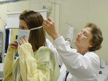 nursing instructor putting a face mask on a nurse