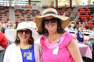 Two women in hats and sunglasses smiling
