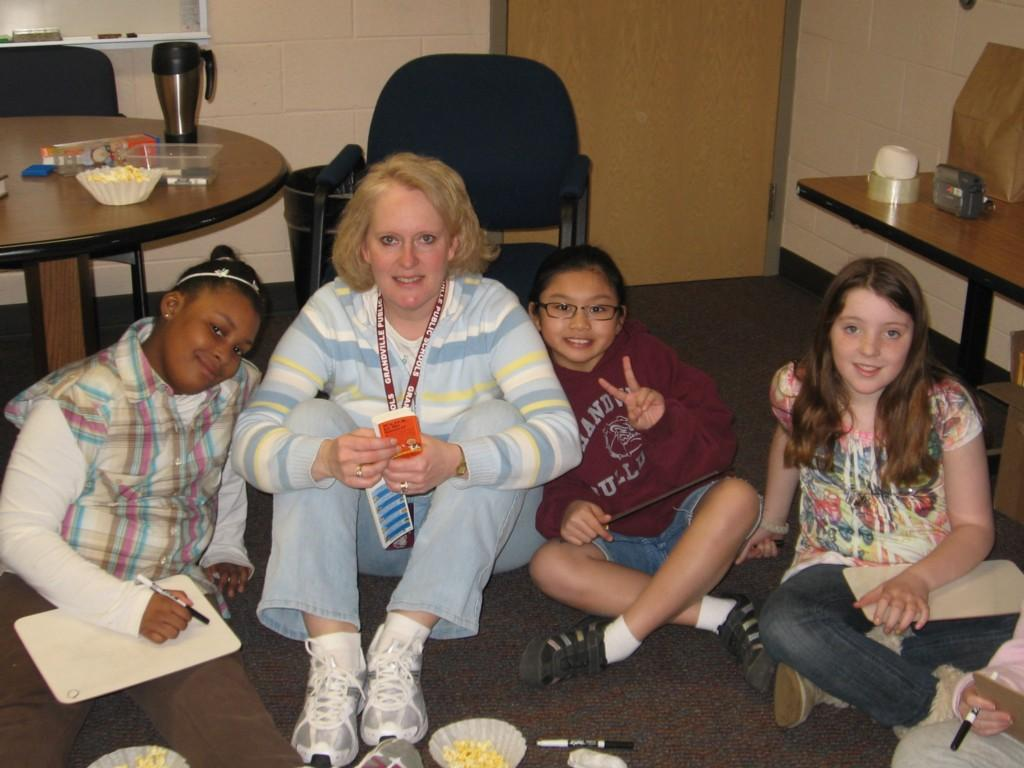 teacher and 3 students sit on floor while eating