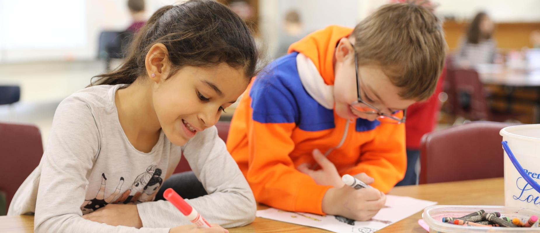 boy and girl color their papers at a table