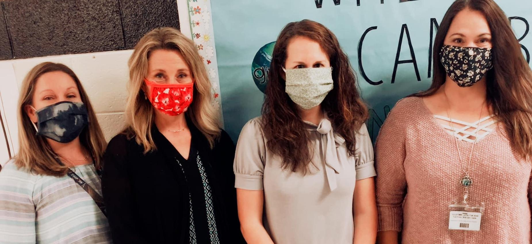 Four teachers wear masks in front of a bulletin board.