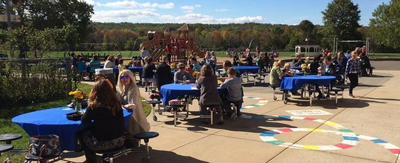 Students and adults enjoy the outdoor Invite Your Parent to Lunch meal