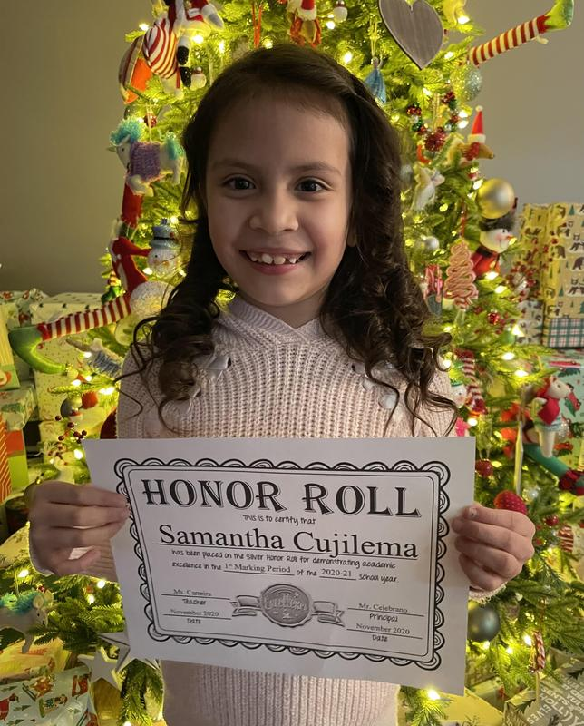 Samantha holding honor roll certificate