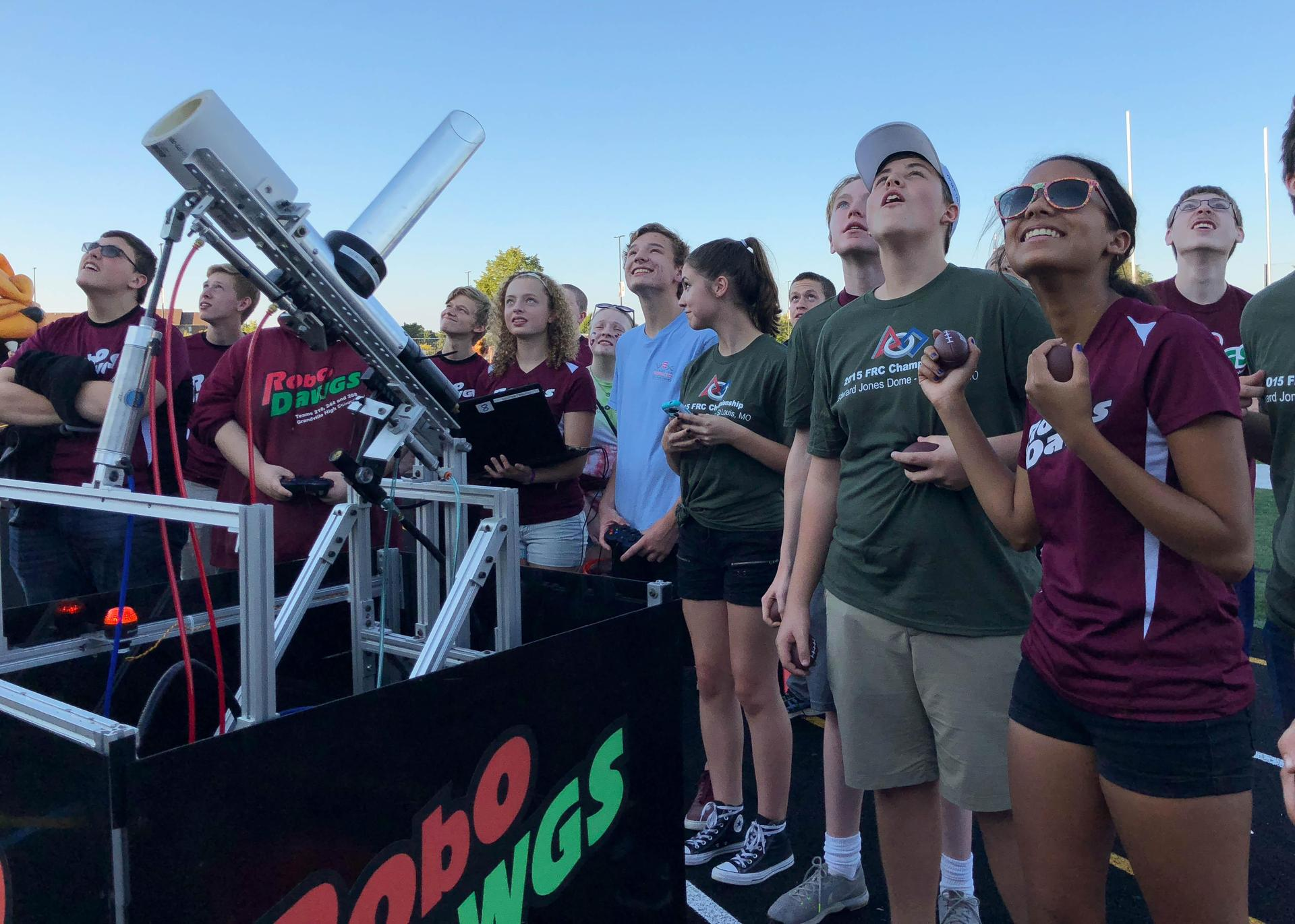 high school robotics students launch t-shirt into stands